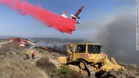 As a bulldozer digs a fire mine, a foot fire plane drops the Bose-check by the Vandenberg Air Force Base near 110 acres.