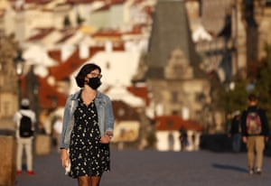 A young woman wearing a mask walks across the medieval Charles Bridge in Prague