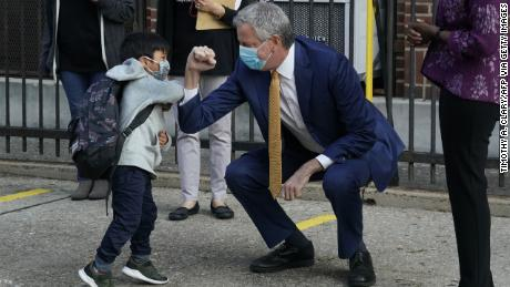 New York City Mayor Bill de Blasio pumps a welcome elbow with a pre-Q student at Queens. The mayor insisted that schools provide in-person training.