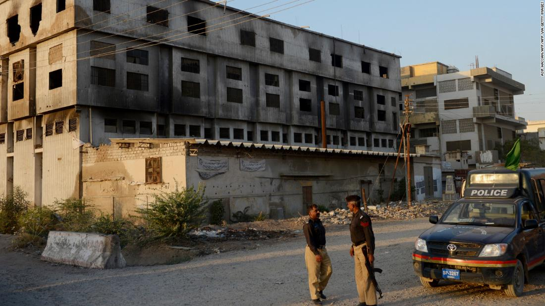 Pakistani policemen stand in front of the burnt out garment factory in Karachi. More than 260 people died in the blaze.