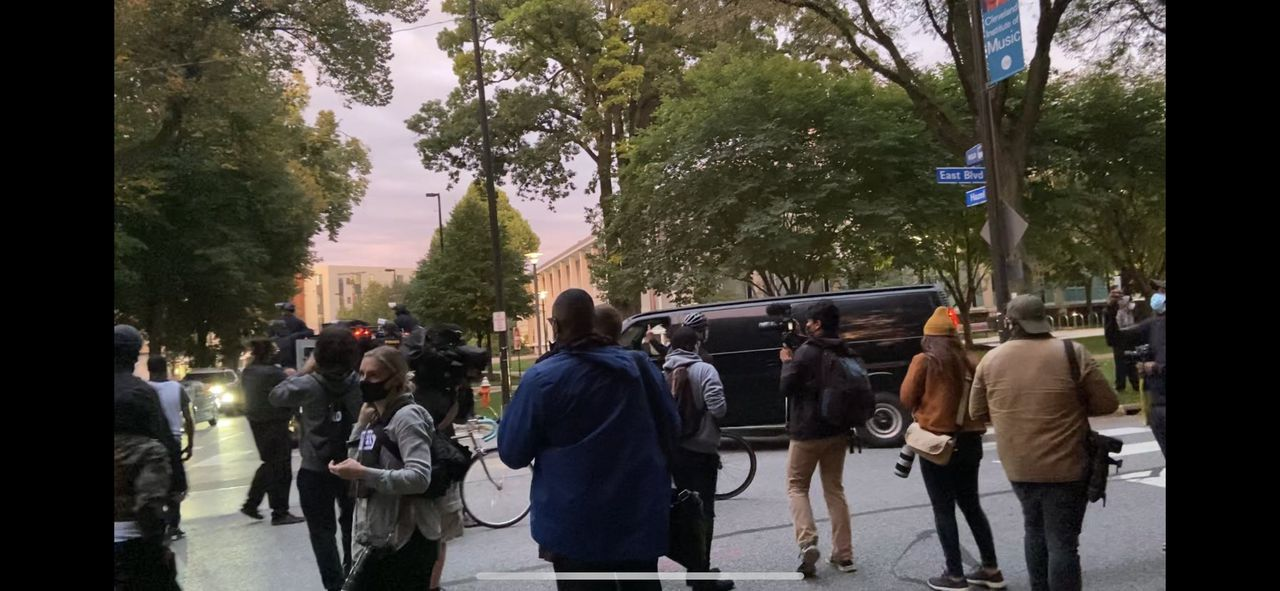 Police caravan driver clears finger at Cleveland Black Lives Matter protesters outside presidential debate