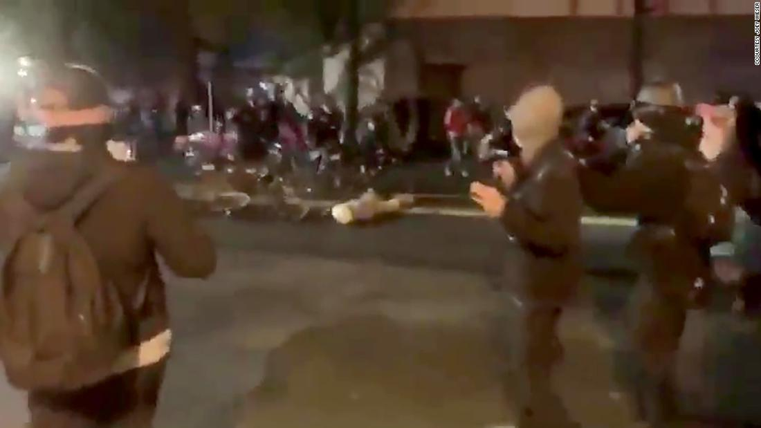 Video shows police officer rolling bike over protester's head
