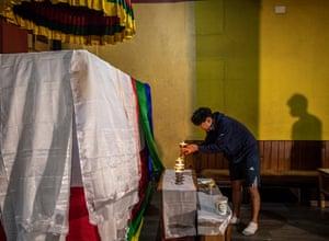 Burba Desiring Sherpa, grandson of Ang Rita Sherpa, lights a candle in front of his coffin in Kathmandu.