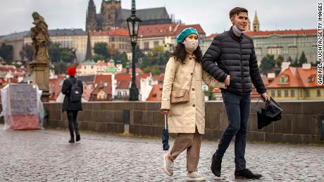 Tourists walk across the medieval Charles Bridge in Prague as the Czech Republic faces a record increase after previously keeping the numbers low.