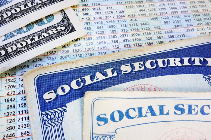 Two Social Security cards and two hundred dollar bills lie on top of the payment sheet.