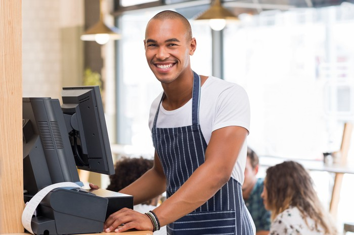 Barista smiling at the register at a coffee shop.