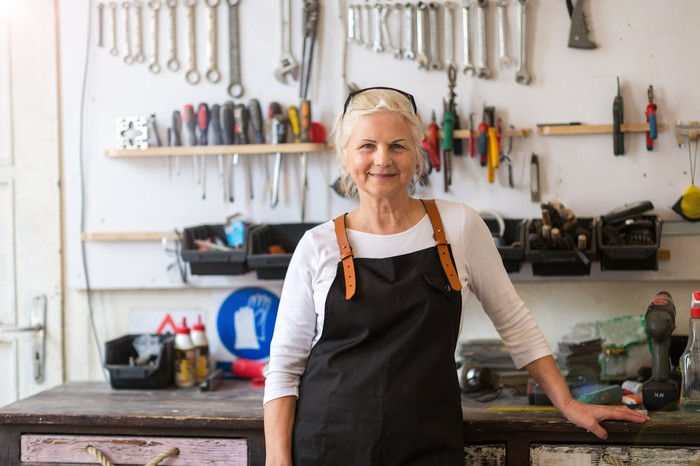 An elderly woman stands in front of a bench in her workshop.