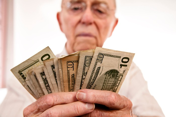 An elderly man is stacking a coin in his hands.