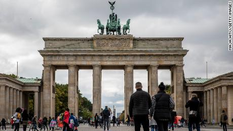 Tourists walk through the Brandenburg Gate in Berlin, Germany on October 12 as meetings are limited to 10 people and a curfew is imposed at 11pm in many regions.