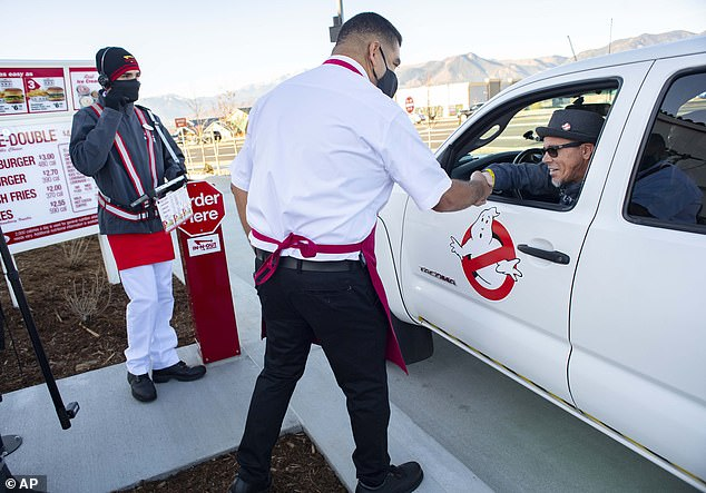 Colorado Springs in-n-out manager Saul Ariola (in white) shakes hands with Ken Wiccini (right), the first person to wait in line at the front line on Tuesday