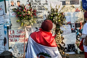 A man wearing the Peruvian flag stands in front of a mural in memory of Indy Sodello and Brian Pintado, two victims of recent struggles.