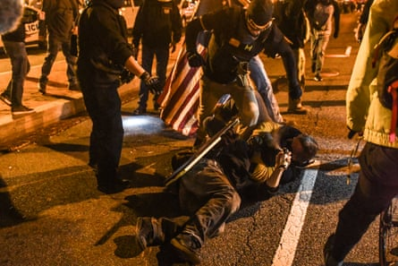Proud Boys members kick a rival opponent on the ground in Washington on Saturday.