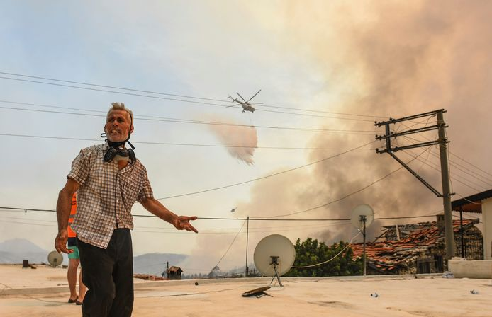 A resident of the village of Sirtkoy, near Manavgat in Antalya province, with a firefighting helicopter in the background.
