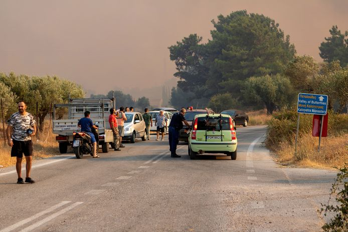 Tourists and locals watch a forest fire near Kalamonas on the Greek island of Rhodes.