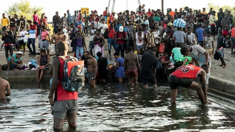 Thousands of migrants camp under an American bridge